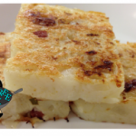 three pieces of fried turnip cake on a white plate