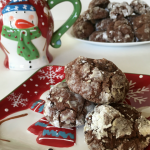 chocolate crinkle cookies on a snowman plate with a snowman cup in the background and a large plate of cookies in the background