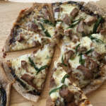 Smoked Duck with Hoisin Sauce Pizza on a wooden cutting board, with two fingers holding one slice