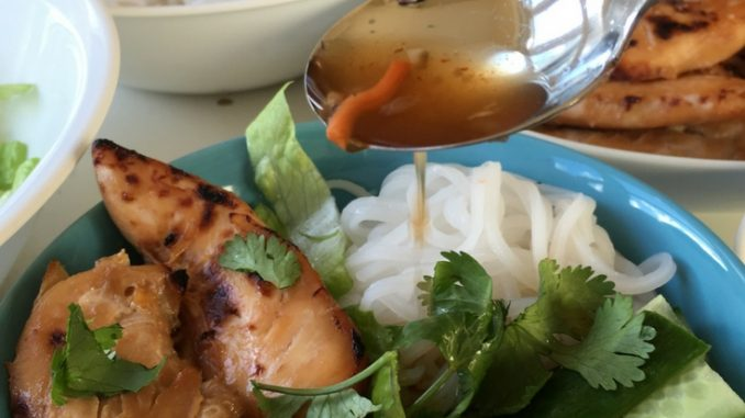 Spoon on some nuoc cham onto vietnamese chicken and rice vermicelli noodles